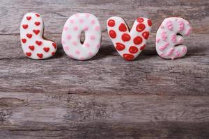 ordet kärleksbokstäver som består av kakor på träbord foto