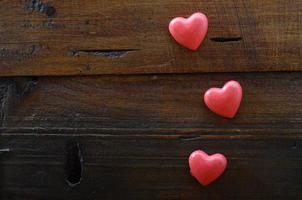 tre röda hjärta på trä bakgrund foto