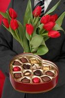 man som håller hjärtformad låda med godis och röda tulpaner foto
