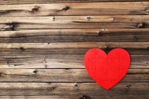 rött pusselhjärta på brun träbakgrund