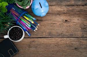 spargris, växter, kaffe, anteckningsbok, pennor och pennor på skrivbordet foto