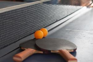närbild orange bollar med bordtennisracketar foto