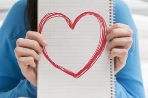 tonårig flicka som håller hjärta i anteckningsboken foto