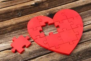 rött pusselhjärta på brun träbakgrund foto