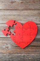 rött pusselhjärta på grå träbakgrund foto
