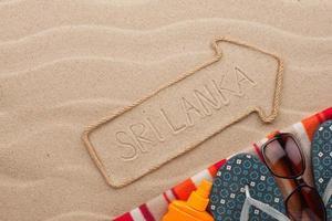 Sri Lanka pekare och strandtillbehör som ligger på sanden foto