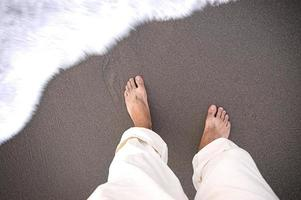 strandfötter och vatten foto