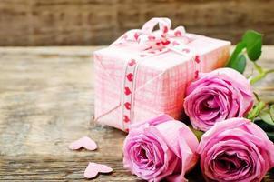 Alla hjärtans bakgrund med gåva och blommor foto