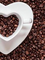 kopp och fat på bakgrund av kaffebönor foto