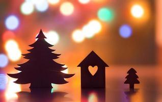 husets silhuett med hål i hjärtform och julgran foto