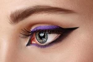 närbild öga med smink - svart och lila pil foto