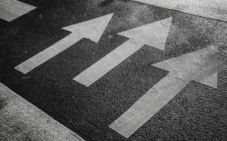 gångmärke vägmärkning med vita pilar på asfalt foto