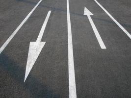 riktningspiltecken på asfaltvägen foto