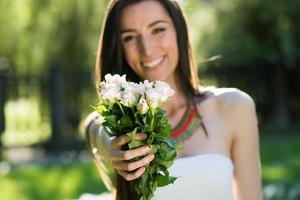 ung kvinna som ger bukett blommor foto