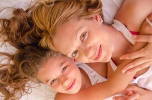 lycklig mor och flicka som lägger i sängen foto