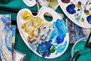 penslar, palett, färg och vatten på bordet
