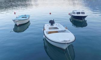 tre små fiskebåtar i lugnt vatten foto