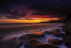 stenig dorset kust vid solnedgången foto