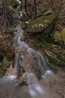 litet vattenfall på berg med stenar och mossa
