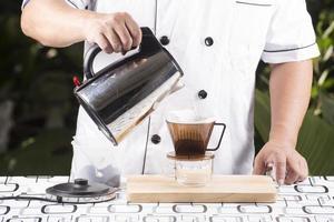 kock som häller varmt vatten till färskt kaffe