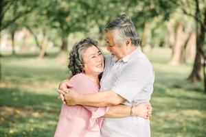 lyckliga äldre asiatiska par som kramar utanför