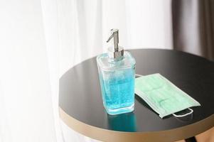 handdesinfektionsmedel och mask på ett bord foto
