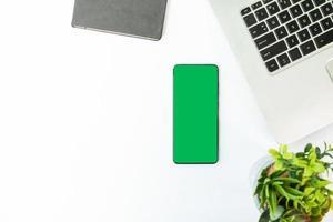 grön skärm smartphone på ett skrivbord med bärbar dator foto