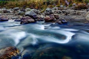 flodvatten som flödar genom stenar i skymningen, sikkim, indien