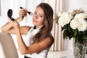 porträtt av vacker ung kvinna får pulver i ansiktet foto