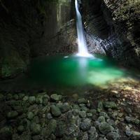 romantiskt vattenfall som rinner genom en spricka till den gröna sjön foto