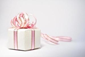 gåva i vit låda med en rosa rosett foto
