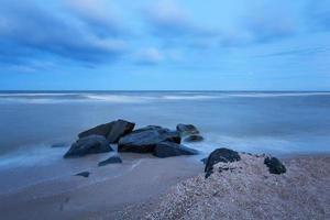 vacker sommarsolnedgång vid havet med stenar