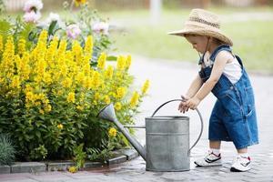 liten pojke med vattenkanna i sommar parkerar