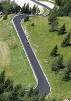 cyklister längs vägen med många kurvor i bergen foto
