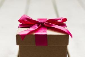 närbild av julklapp med rosa band foto