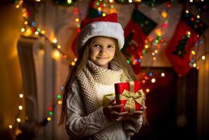 porträtt av leende flicka som öppnar mousserande presentask vid jul foto