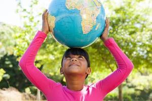 söt liten flicka som håller världen foto