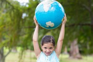 liten flicka som håller en jordglob foto
