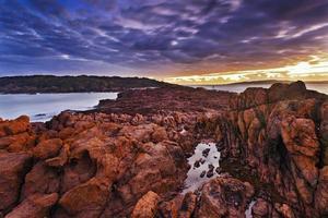 havet stor stenig solnedgång foto