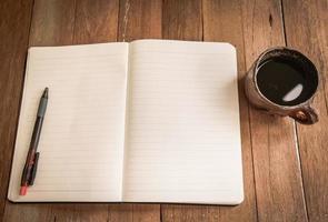 anteckningsbok och kaffekopp på träbakgrund