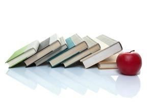 böcker som lutar sig på sidan med ett äpple framför foto
