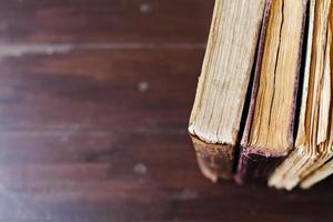 vintage böcker på mörk trä bakgrund, selektiv fokus foto