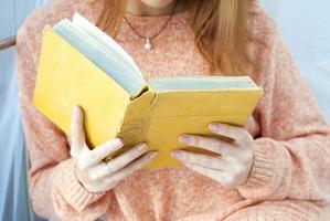 ung flicka som läser en gammal bok foto