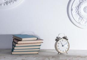 hylla med böcker och en väckarklocka foto