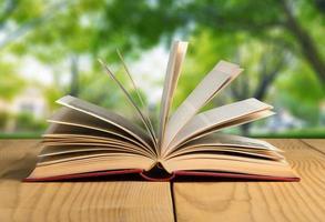 bok. öppen bok på träplankor över abstrakt ljus bakgrund foto