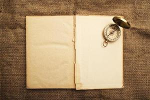 gammal öppen bok med kompass foto