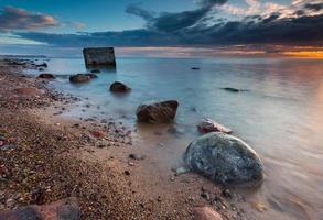 stenig havsstrand med gammal bunker i havet