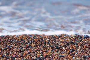 färgglada stenar på stranden nära havet foto