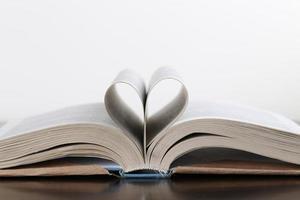 öppen bok på träbord över vit bakgrund. vikta sidor foto