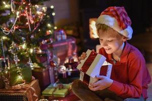 jul, liten pojke som öppnar en gåva nära trädet tänds foto